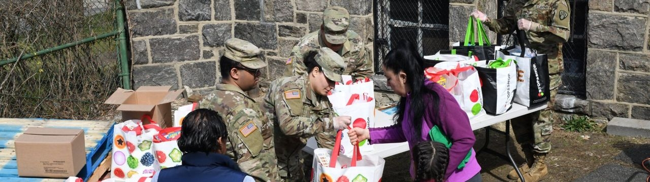 New York National Guard Soldiers from the 101st Signal Battalion hand groceries to members of the community at a food distribution point at Hope Community Services in New Rochelle on March 18, 2020.