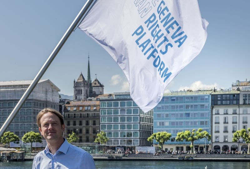 Felix Kirchmeier, Director of the plaform, in front of the flags of the Geneva Human Rights Platform on the Mont-Blanc Bridge
