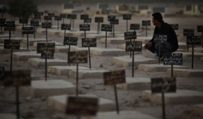 Iraq,  A worker of the Al-Zubai centre tends to graves of recovered but unidentified casualties of war.