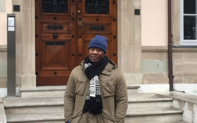 Tafadzwa Christmas, a Zimbabwean student enrolled in the Master of Advanced Studies in Transitional Justice, Human Rights and the Rule of Law in front of the Villa Moynier, the Geneva Academy's headquarters